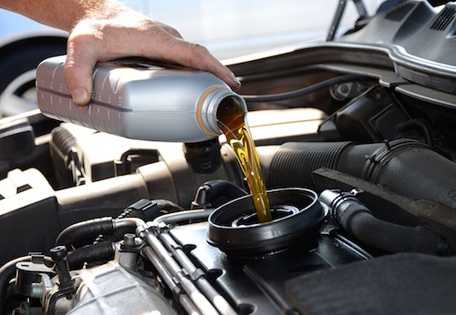 hand pouring oil into a car engine.