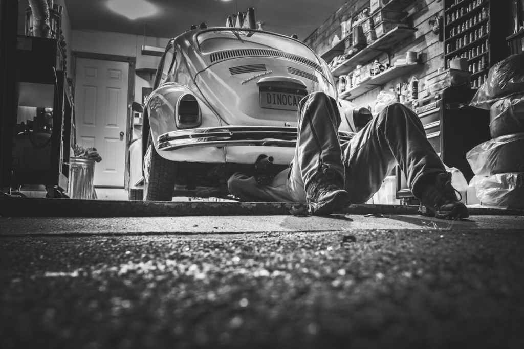 buying a used car—man working on white VW bug in garage.